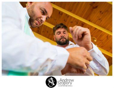 groomsmen helping groom put on his cuff lings