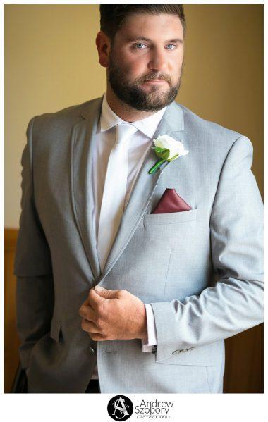 formal portrait photo of groom in window light