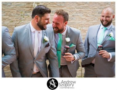 formal portrait photo of groom and groomsmen outside laughing