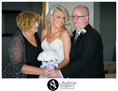 bride and mum looking at dad laughing during family photo