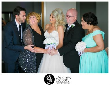 bride, mum, dad and siblings looking at brother laughing during family photo