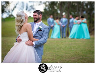 Bride and groom laughing as they interact with bridal part in the background