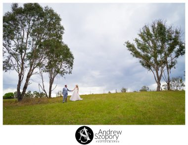 groom walks and leads bride down a hill together