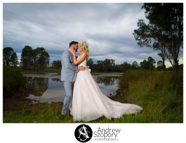 dramatic formal picture of bride and groom hugging by the dam