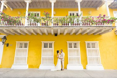 Bride and groom stand in front of colourful house in Cartagenta at El Marques