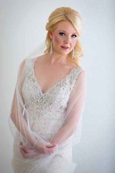 bridal-portrait-in-window-light holding veil