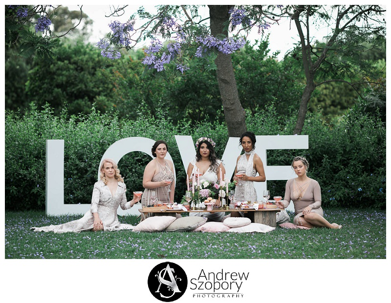 bride to be and bridesmaids sit under Jacarander tree having a cocktail during bridal party